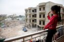 A Syrian girl waves from the balcony of an unfinished apartment block in northern Lebanon (11173940763).jpg